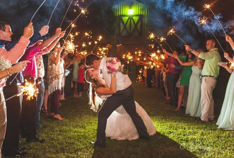 wedding guests with sparklers cheering bride and groom